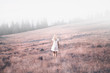 Back view of a woman in white dress walking on countryside meadow. Retro color tone filter effect used.