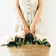 Young pretty woman in linen dress holding straw bag with white peony flowers on white background.