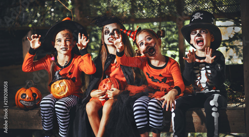 Leinwanddruck Bild happy Halloween! a group of children in suits and with pumpkins in forest.