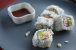 Maki on plate with cup of soy sauce