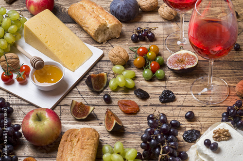 Poster Cheese, wine, baguette grapes figs honey and snacks on the rustic wooden table top.