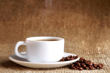 Cup of hot coffee with beans on wooden background