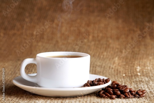 Cup of hot coffee with beans on wooden background - 219254439