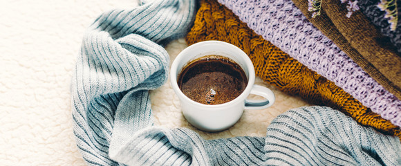 A mug of coffee on a white blanket and a pile of knitted clothes, long banner © yakovlevadaria