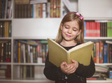 Cute little schoolgirl holding book and reading - 219260484