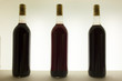 Three bottles of red wine with different tones
