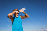 athletic man drinking water from sports bottle