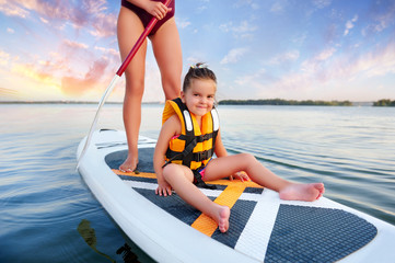 Mother paddling with little daughter on sup board