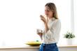 Beautiful young woman eating yogurt at home