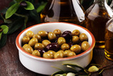 Olives. Bottle virgin olive oil and oil in a bowl with some olives - 219306270
