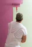 Young man is painting wall with roller - 219311471