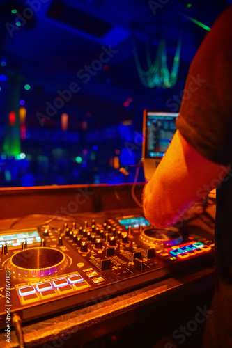 dj mixes the track in the nightclub at party dj hands in motion