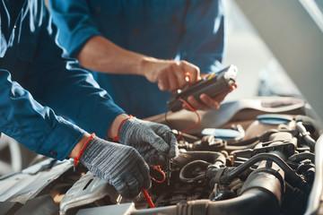 Mechanics using multimeter when checking work of car engine in garage