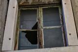 Broken window glass. Rotten frames. Abandoned building.