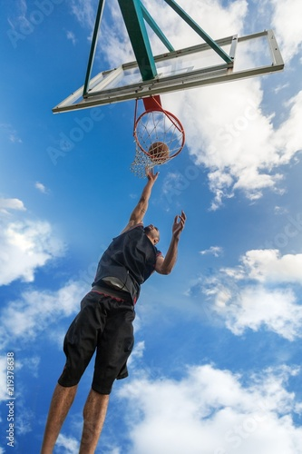 Fototapeta Low Angle View of Basketball Player Dunking Ball
