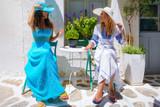 Zwei junge Touristinnen in Sommerkleidern genießen ihren Urlaub auf einer Insel auf den Kykladen in Griechenland  - 219385499