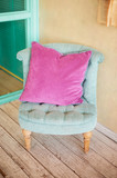 Turquoise chair in pink pillow in pastel colors. Stylish interior
