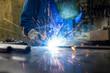 Leinwanddruck Bild - Schweißer in seiner Werkstatt beim Schweißen von Metall