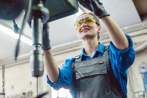 Leinwanddruck Bild Arbeiterin in Schlosserei arbeitet an der Bohrmaschine