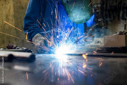 Leinwanddruck Bild Schweißer in seiner Werkstatt beim Schweißen von Metall