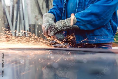 Leinwanddruck Bild Metallarbeiter in Fabrik schleift Werkstück und Funken fliegen