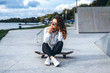 Cute girl with curly hair with skateboard in the park