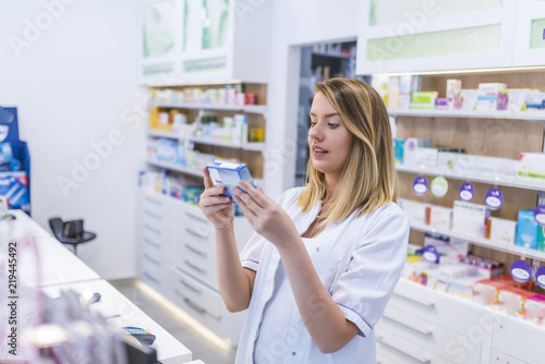 Beautiful smiling female pharmacist working in a pharmacy (or drugstore) with customer friendly attitude