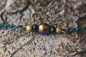 Hematite bead with rainbow color effect bracelet on wooden background © marbenzu