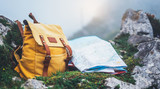 Hipster hiker tourist yellow backpack and map europe on background green grass nature in mountain, blurred panoramic landscape, traveler relax holiday concept, view planning wayroad in trip vacation - 219459639