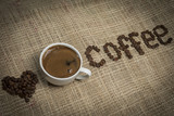 Cup of coffee and letters coffee on a hessian background.