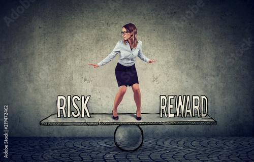 Skillful young business woman balancing between reward and risk