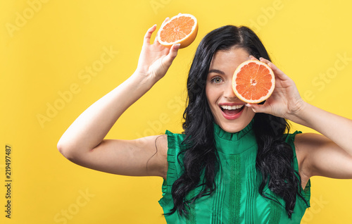 Happy young woman holding oranges on a yellow background - 219497487