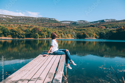 Person sitting on peer by the lake
