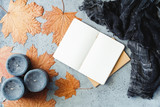 Autumn flat lay composition on a grey concrete background. Maple leaves, the open notebook with empty sheets, black aromatic candles and warm scarf. Mockup, top view. - 219512466