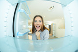 Woman looking excitedly into empty fridge - 219521002