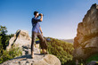 A traveler man standing on the rocks and holding backpack and binoculars over the blue sky background