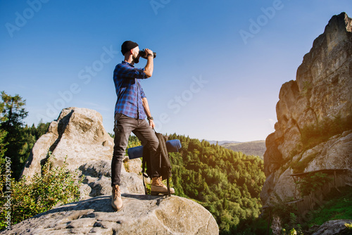 Fototapeta A traveler man standing on the rocks and holding backpack and binoculars over the blue sky background