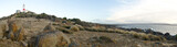 Panoramic view of Low Head Lighthouse, Tasmania, Australia, showing the dry foreground with button grass and rocky coastline.