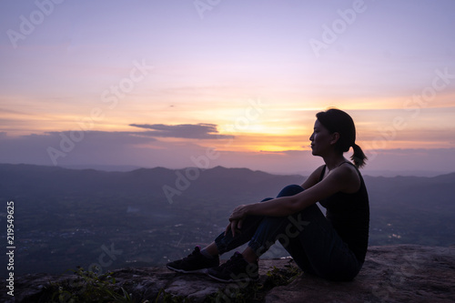 silhouette woman sitting on mountain - 219549625
