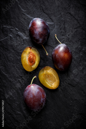 Fresh plums on a black background, top view - 219573857