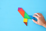 rocket made from tangram puzzle on blue pastel wooden background - 219584292