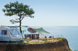 A house on wheels and a canopy under a tree on a cliff by the sea