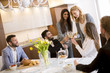 Young friends having dinner at home and toasting with white wine - 219630603