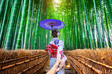 woman wearing japanese traditional kimono holding man's hand and leading him to Bamboo Forest in Kyoto, Japan. © tawatchai1990