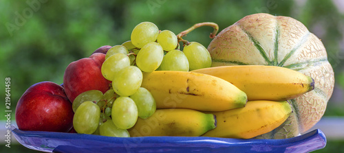 Set of fruit, melon, bananas, grapes and peaches, on a tray with green background