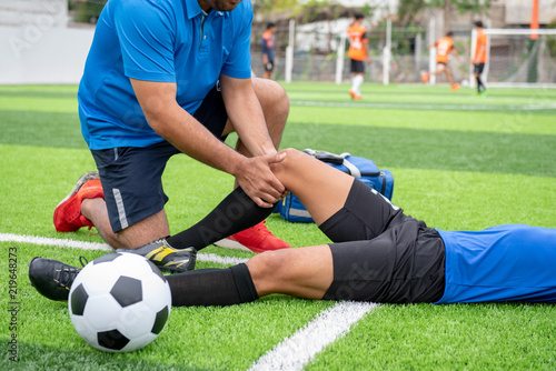 Footballer wearing a blue shirt, black pants injured in the lawn during the race.