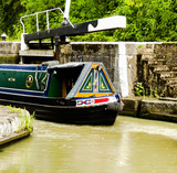 Unidentifiable colourful narrowboat passing through open lock gate in the Stockton flight on the Grand Union Canal, Stone steps in background. Warwickshire - 219648827