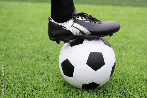 The foot of the footballer stands on the lawn.