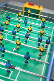 Table football with players with numbers kicking ball