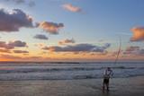 Scène de pêche en mer. Pêcheur en surf casting en action entrain de lancer. pêche du bord sur une plage - 219666207
